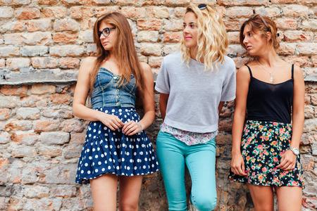 spring time: Three teenage girls looking at something interesting