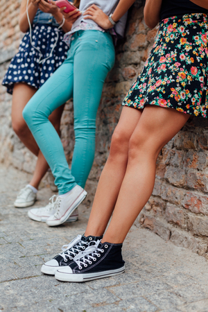 Three pretty girls leaning against a wall Stock Photo