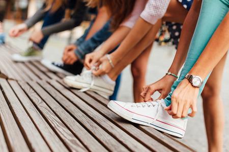 binding: Group of teenage girls binding shoelaces