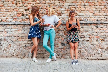 chicas adolescentes: Tres adolescentes que se divierten en el smartphone