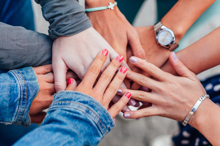 support group: Girls putting their hands on top of each other. Hands together.