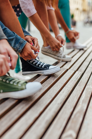 Girls binding shoelaces  on the bench at the same time Stock Photo