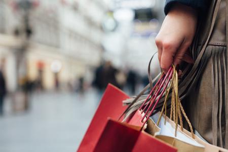 コピー スペースが付いている通りの shopiing 袋を保持している女性のクローズ アップ 写真素材