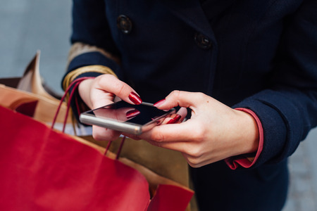 with bag: Woman in coat texting on mobile phone after shopping