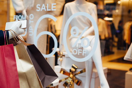 Woman with shopping bags and mobile phone in front on store window with copy space