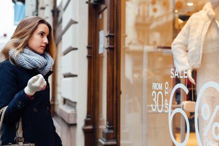 ブティックのショーケースを見てスカーフと冬の手袋でエレガントな女性 写真素材