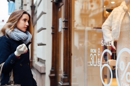 tienda de ropa: Mujer elegante con los guantes de la bufanda y del invierno mirando escaparate de boutique