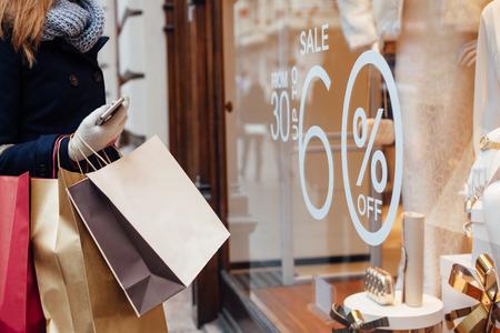chicas de compras: Detalle de mujer con bolsas de la compra frente a la ventana de almacén