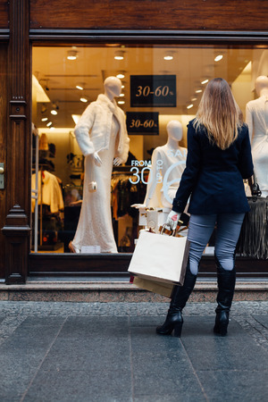 front of: Woman standing in front of shopping window Stock Photo