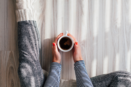 warms: Top view of woman warms his hands on a hot cup of coffee Stock Photo