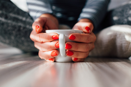 warms: Woman warms his hands on a hot cup of coffee