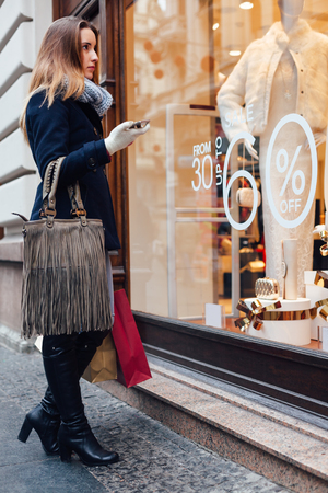 Elegant woman looking at boutique showcase with a discount from 30 to 60 percent