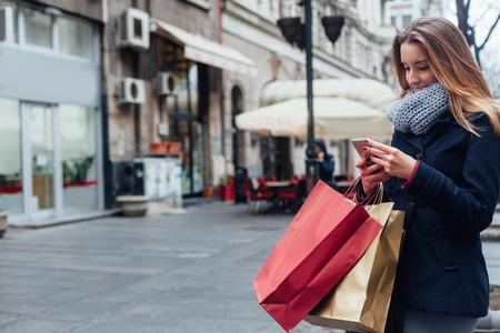 chicas de compras: Mujer feliz texting en su teléfono móvil en la calle con espacio de copia