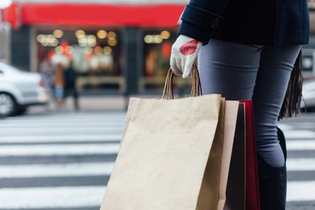 Closeup of woman with shopping bags waiting at the pedestrian crossing Stock Photo