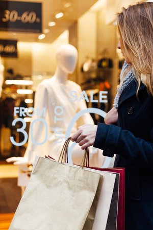 Closeup of woman holding shopping bag in front of boutiques