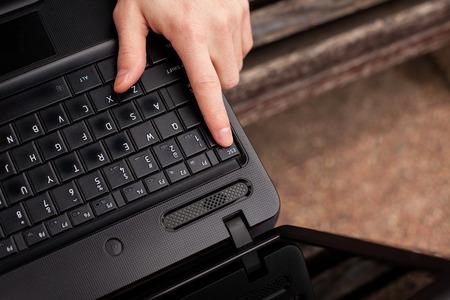 esc: Man pressing Esc on the laptop. Stock Photo