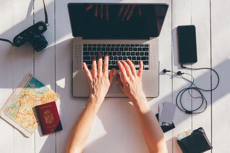 city trip: City trip travel planning essentials. Woman looking travel destinations on laptop.