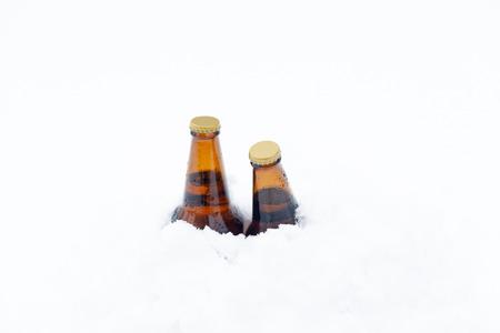 freshly fallen snow: Two unopened bottles of beer covered to the neck in freshly fallen snow