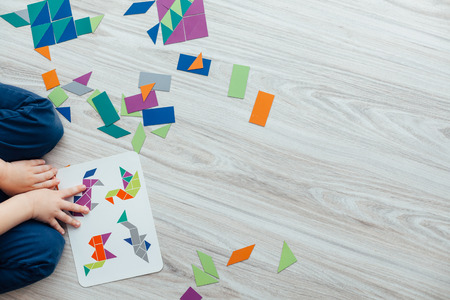 puzzle people: Kid playing with geometric shapes on the floor with copy space