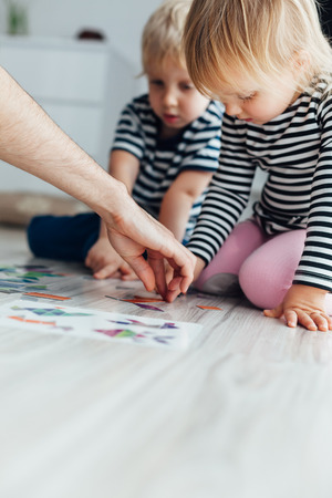 Dad teaching children to play puzzle
