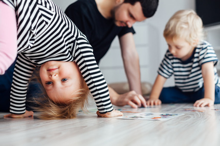 puzzle: Father playing puzzle with children. Girl doing exercises on the floor.