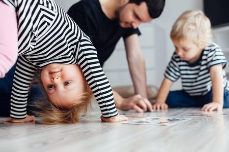 suelos: Padre jugando con los niños rompecabezas. Chica haciendo ejercicios en el suelo.