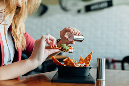 adds: Woman adds pepper for a tasty meal in a restaurant