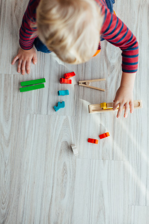 Little boy playing with wooden colorful toys