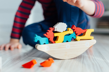 Closeup of little boy playing with wooden colorful toys