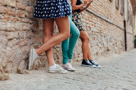 girl legs: Three pretty teen girls leaning against a wall Stock Photo