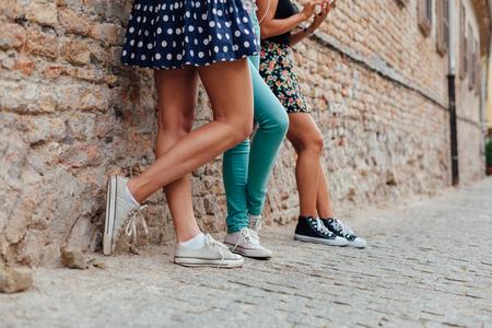 ragazza innamorata: Tre ragazze teenager graziosa che si appoggia contro un muro