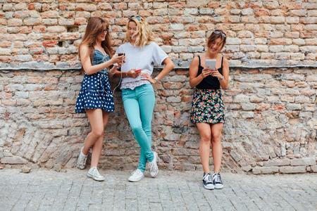 modern generation: Modern generation. Three teenage girls are having fun on smartphone outdoors. Stock Photo