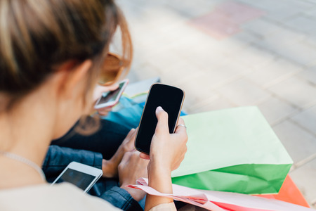 after shopping: Girl touching new smart phone after shopping Stock Photo
