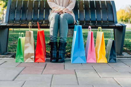 Girl sitting with colorful bags. Holiday gifts aftter shopping