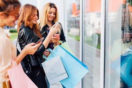 Primer plano de hermosas muchachas que usan los teléfonos móviles fuera de una tienda Foto de archivo - 52017922