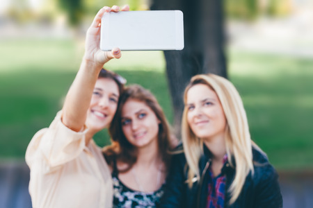 self   portrait: Girls making self portrait with front camera on new mobile phone Stock Photo