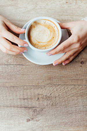 Closeup of female hands holding a cup of coffee with foam on wooden table. Top view, copy space.