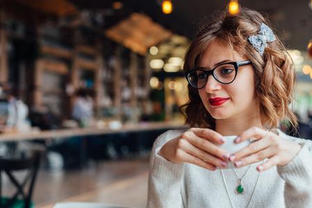 chicas sonriendo: La mujer bastante joven en un caf� mirando a alguien