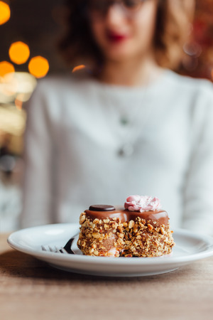 Closeup of woman with chocolate cake on wooden table in a cafe