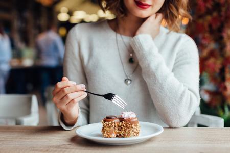 Primer de la mujer que come la torta de chocolate en un café Foto de archivo