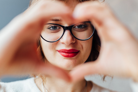 Woman making heart shape with hands in closeup