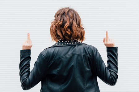 fuck: Hipster woman show middle finger, fuck you off sign in front of a white wall. Outdoor funny lifestyle portrait, concept of brutal, punk, furious, indecent.