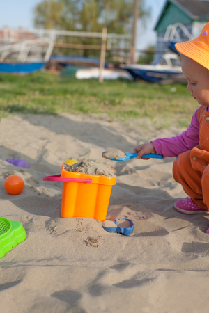 plastic toys: Little girl playing in the sand with plastic toys Stock Photo