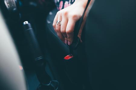 fastening: Woman fastening seat belt in car