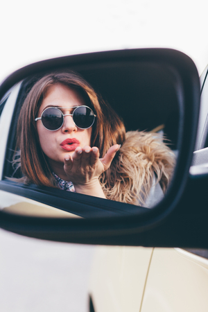 rear view girl: Woman with sunglasses sending kiss at mirror Stock Photo