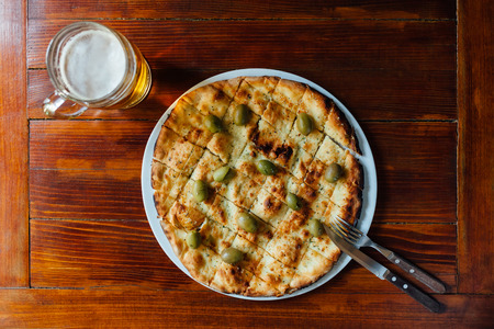 olio: Top view of delicious Aglio Olio Pizza and Beer Mug on wooden table. Stock Photo