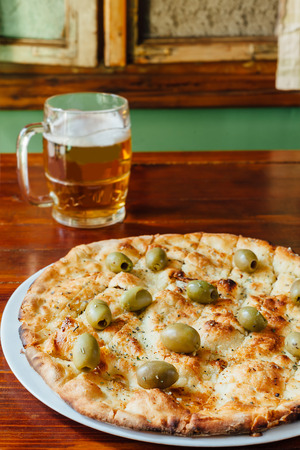 olio: Delicious Aglio Olio Pizza and Beer Mug on wooden table in a rustic restaurant. Ingredients marinade of olive oil, garlic, basil, oregano, olives. Stock Photo