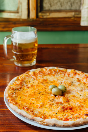margarita pizza: Delicious Margarita Pizza and Beer Mug on wooden table in a rustic restaurant. Ingredients peeled tomato, cheese, olives, oregano.