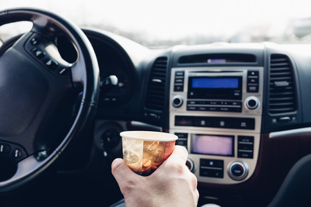 go inside: Man with coffee to go driving car
