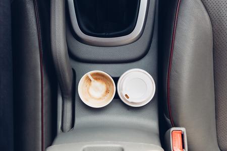 Closeup of coffee cups inside car holder between seats